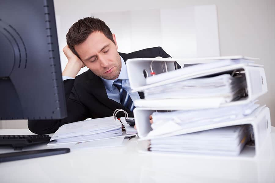 Businessman asleep at desk, in front of a stack of files