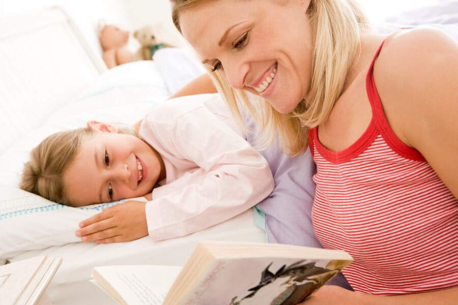 Mother reading a bedtime story to her young daughter