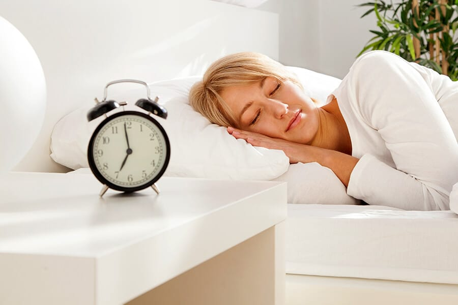 Woman asleep in bed, with the alarm clock pointing away from her