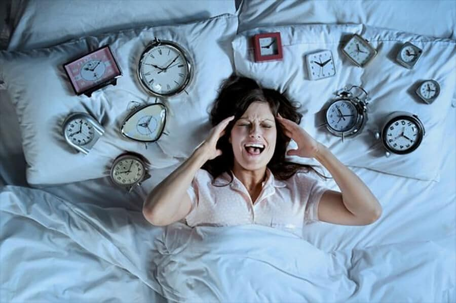 Woman in bed surrounded by alarm clocks